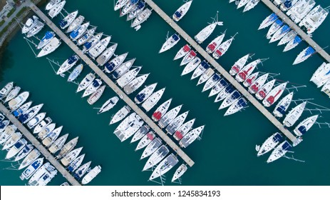 Aerial view of a lot of white boats and yachts moored in marina on a turquoise water, during a summer season