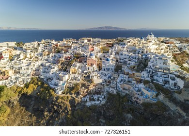 Aerial view of white cave houses on the steep cliff in Oia, Santorini Island, Greece