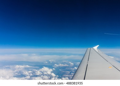 Aerial View of white cloud, blue sky and aircraft wing