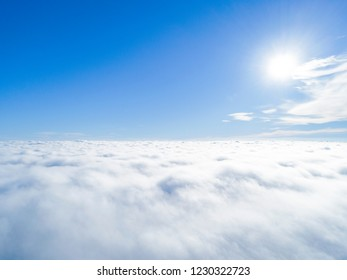 Aerial view White clouds in blue sky. Top. View from drone. Aerial bird's eye look. Aerial top view cloudscape. Texture of clouds. View from above. Sunrise over clouds