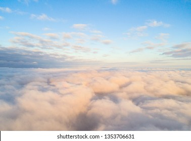 Aerial view White clouds in blue sky. Top view. View from drone. Aerial cloudscape. Texture of clouds. View from above. Sunrise or sunset over clouds