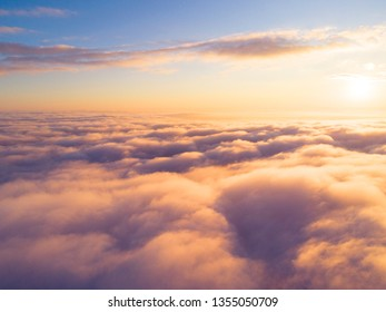 Aerial view White clouds in blue sky. Top view. View from drone. Aerial bird's eye. Aerial cloudscape. Texture of clouds. View from above. Sunrise or sunset over clouds