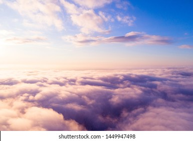 Aerial view White clouds in blue sky. Top view. View from drone. Aerial bird's eye clouds. Aerial top cloudscape. Texture of clouds. View from above. Sunrise or sunset over clouds