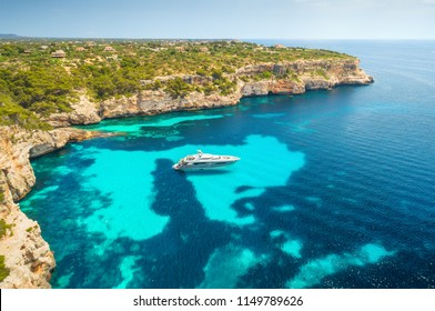 Aerial view of white luxury yacht and transparent sea at sunny day in Mallorca, Spain. Colorful summer landscape with bay, boat, green trees, rocks, blue water, sky. Balearic islands. Top view. Travel
