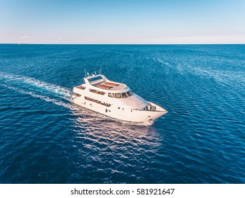 Aerial view of the white motor yacht sailing in the blue sea during summer vacation