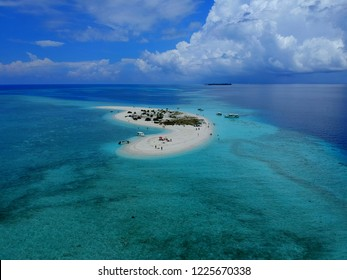 The aerial view of the white sandbank surrounded by coral reef and beautiful blue ocean near Male, Maldives