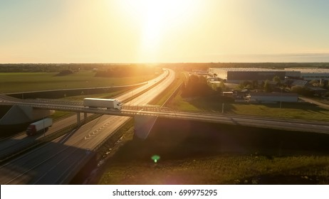 Aerial View of White Semi Truck with Cargo Trailer Passing Highway Overpass/ Bridge. Eighteen Wheeler is New, Loading Warehouses are Seen in the Background.