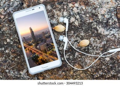 Aerial view of white smart phone with bangkok city at twilight time view of taksin bridge and chaopraya river with headphones on stone background.