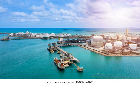 Aerial view white storage tank of crude oil and natural gas and petrochemical product at oil and gas terminal industry port, Business power and energy fuel petroleum logistic by tanker cargo freight.
