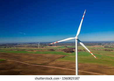 Aerial view of white wind turbines in a field