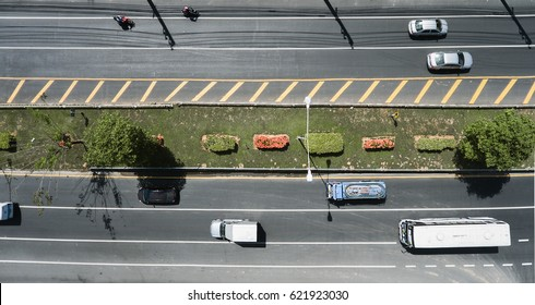 Aerial view of the wide road with a nice dividing strip of grass, flowers and trees.Top view of moving cars and buses.Flat illustration of road traffic.