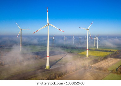 Aerial view of wind energy turbines on windfarm above mist layer on german countryside in the morning sun. Germany