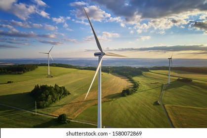 Aerial view of wind turbine farm. Wind power plants in green landscape against sunset sky with clouds. Aerial, drone inspection of wind turbine.