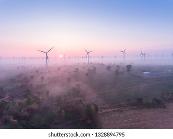 Aerial view of wind turbine sunrise in forested  with fog . Sustainable development, environment friendly, renewable energy concept.