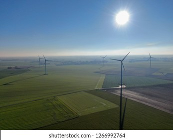 Aerial view of wind turbines and agricultural fields on a beautiful blue winter day - Energy Production with clean and Renewable Energy - aerial shot, analog image style