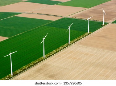 Aerial view of wind turbines and agricultural fields, Aerial shot of the windmills on the green field, Aerial photography of wind power generators.