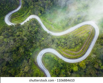An aerial view of a winding road cutting through a forest in Cameron Highlands, Malaysia