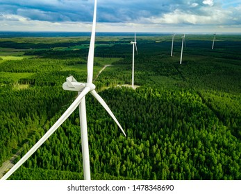 Aerial view of windmills in green summer forest in Finland. Wind turbines for electric power with clean and Renewable Energy