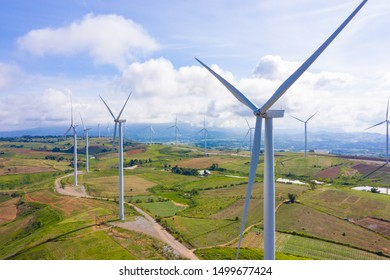 Aerial view of windmills rotating by the force of the wind for generating clean renewable energy for sustainable development in a green ecologic way on beautiful cloudy sky at highland.