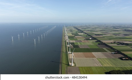 Aerial view of windpark in the Dutch Noordoostpolder, Flevoland and the IJsselmeer, near the town of Urk. Left half of the photo is water, right side of the photo is farmland.
