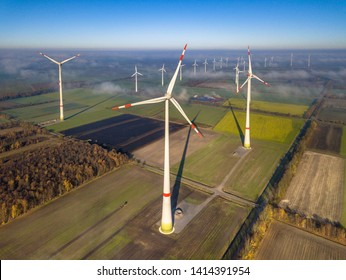 Aerial view of windturbines in the wind above mist layer on german countryside in the morning sun. Germany