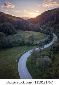Aerial view of a windy road in the Jura mountains in Switzerland leading to a colourful sunset with orange clouds