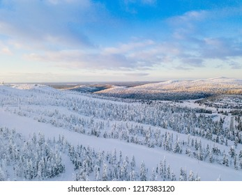 Aerial view of winter forest with frosty trees, rural road and village in Finland, Lapland