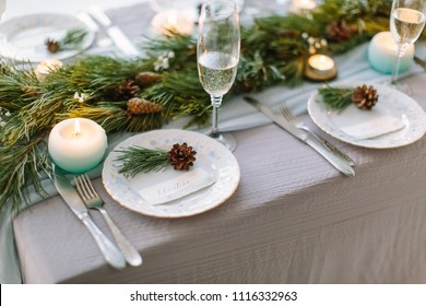 Aerial view of winter green garland on a wedding table with white plates and and blue candles