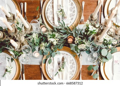 Aerial view of winter green garland on a wedding receptions head table with gold place setting and candelabra