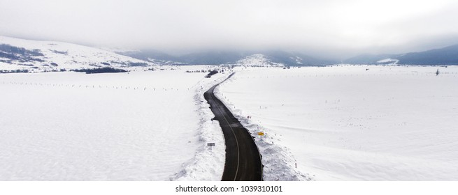 Aerial view of winter landscape with straight open road