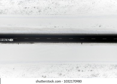 Aerial view of winter road in snowy fields. Drone captured shot from above.