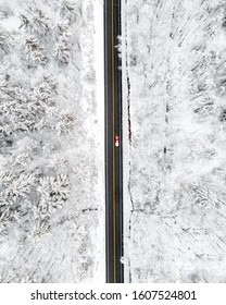 Aerial view of a winter scene with a car driving down a country road during a snow storm