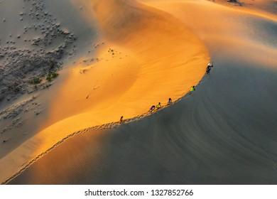 Aerial view of Woman carrying basket at sunset in Bau Trang sand dune, as sun gradually create beautiful setting near paradise beach in Mui Ne, Phan Thiet, Vietnam.