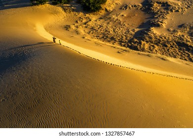 Aerial view of Woman carrying basket and children at sunset in Bau Trang sand dune, Mui Ne, Binh Thuan, Vietnam