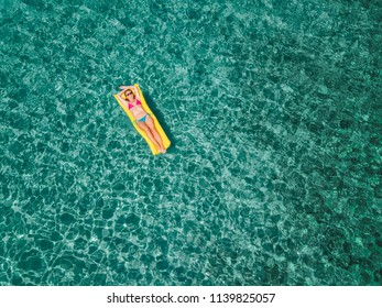 Aerial view of woman floating on the water mattress in the turquoise sea