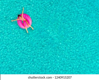 Aerial view of woman floating on inflatable donut shaped mattress, sunbathing.