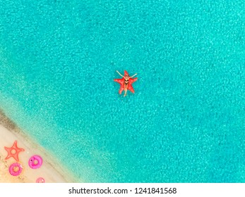 Aerial view of woman floating on inflatable star fish mattress by sandy beach and inflatable rings.