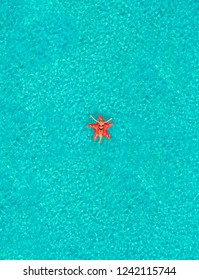 Aerial view of woman floating on inflatable star shaped mattress with arms up in the air on transparent sea.