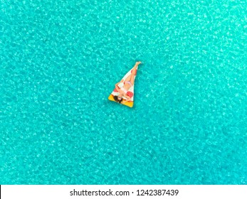 Aerial view of woman floating on inflatable pizza mattress, sunbathing on transparent sea.