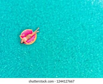 Vista aérea de una mujer flotando sobre un colchón inflable en forma de burro, relajándose en un mar transparente.