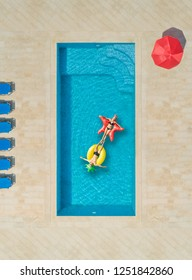Aerial view of woman and a man on inflatable mattress in swimming pool surrounded by deck chairs and parasol.