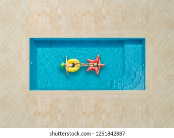 Aerial view of woman and a man on inflatable mattress in swimming pool.