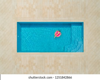 Aerial view of woman on donut inflatable mattress in swimming pool.