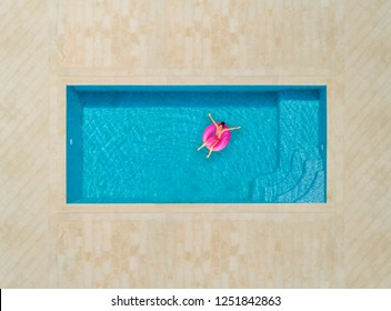 Aerial view of woman on a inflatable flamingo mattress in swimming pool.