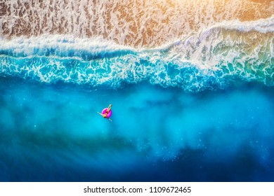 Aerial view of woman swimming on the pink swim ring in the transparent sea in Oludeniz. Summer seascape with girl, beach, beautiful waves, blue water at sunset. Top view. Travel and holiday. Resort
