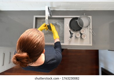 Aerial view of woman washing dishes in home kitchen sink
