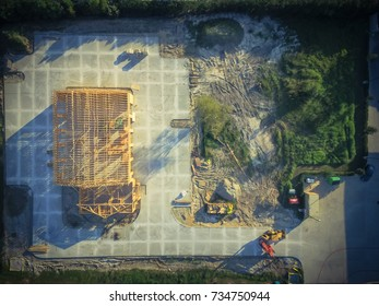 Aerial view wood frame house under construction with foundation in Humble, Texas, USA. New stick built framing one floor commercial building. Excavator, bulldozer and pile of logs, sand. Vintage tone