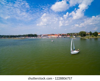 Aerial view of yacht sailing on Niegocin Lake, Gizycko town in the background, Mazury, Poland