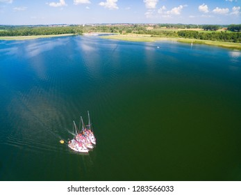 Aerial view of yachts sailing on Mamry Lake, concrete quay and town beach in the background, Wegorzewo, Mazury, Poland