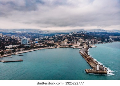Aerial view of Yalta embankment from drone, old Lighthouse on pier, sea coast landscape and city buildings on mountains, beautiful winter panorama of European resort, Crimea